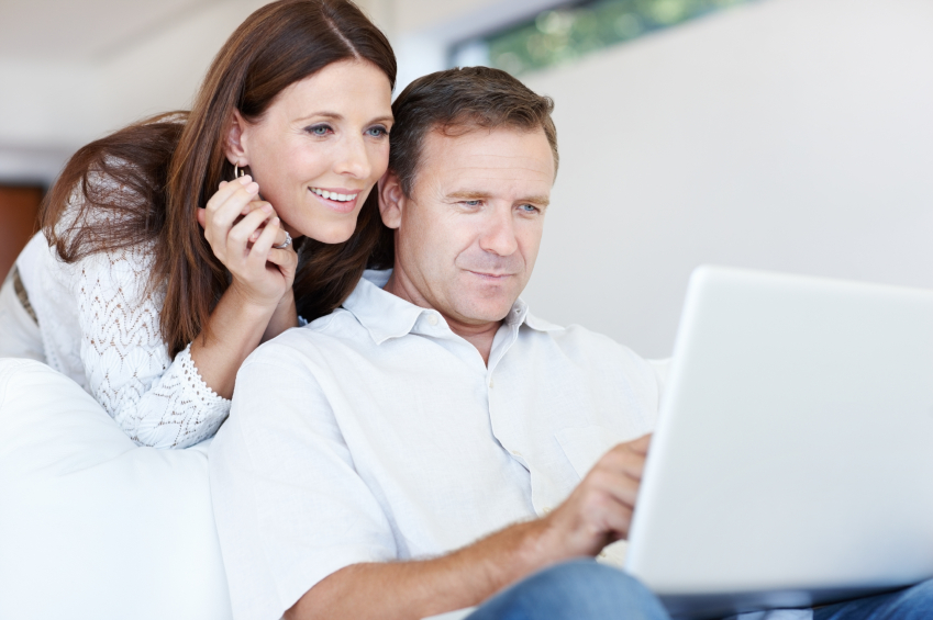 Portrait of mature couple browsing net together on laptop at home