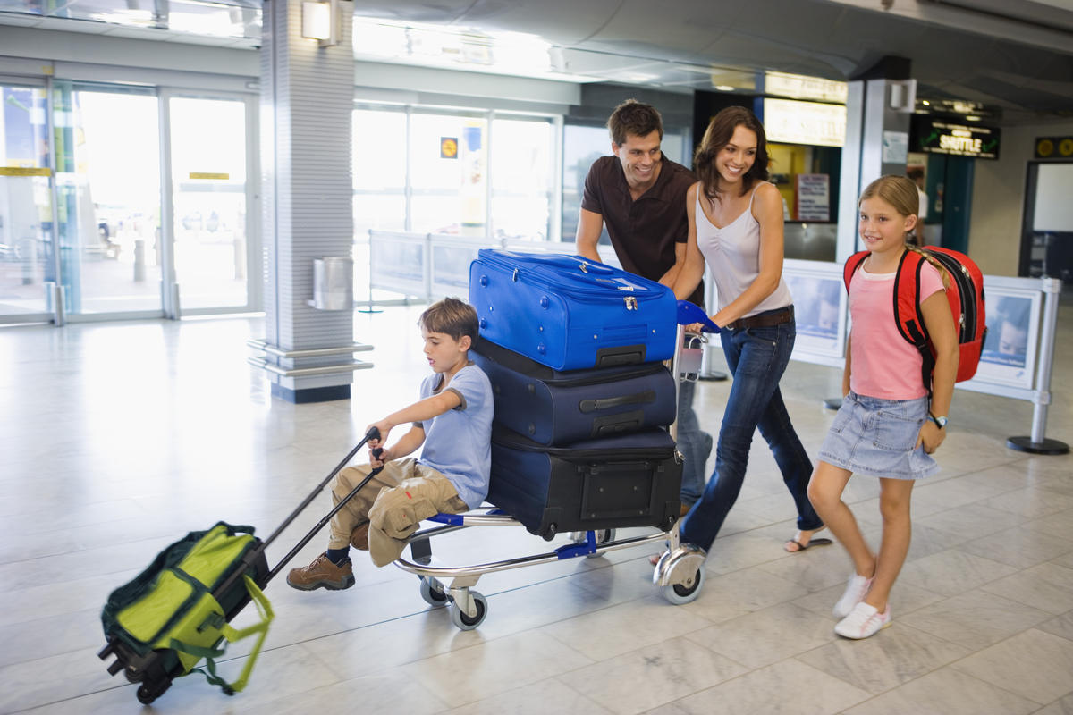 Family with cart of luggage in airport